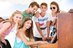 Teenagers at summer music festival, girl plays the piano. Group of teenage boys and girls at summer music festival, beautiful young women plays the piano. Sunny Royalty Free Stock Photos