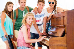 Teenagers at summer music festival, girl plays the piano. Group of teenage boys and girls at summer music festival, beautiful young women plays the piano. Sunny Royalty Free Stock Images