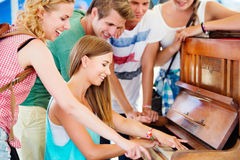 Teenagers at summer music festival, girl plays the piano. Group of teenage boys and girls at summer music festival, beautiful young women plays the piano. Sunny Royalty Free Stock Image