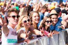 Teenagers at summer music festival having good time. Teenagers at summer music festival under the stage in a crowd enjoying themselves, showing peace sign Royalty Free Stock Photography