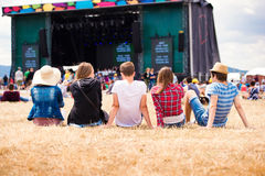 Teenagers, summer music festival, sitting in front of stage. Group of teenagers at summer music festival, sitting on the grass in front of stage, rear view Stock Image