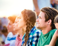 Teenagers at summer music festival, sitting on the ground Royalty Free Stock Image