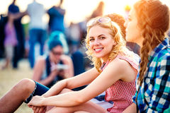 Teenagers at summer music festival, sitting on the ground Stock Photos