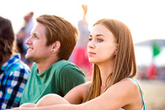 Teenagers at summer music festival, sitting on the ground Royalty Free Stock Photos