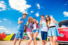 Teenagers at summer music festival by vintage red campervan Royalty Free Stock Image