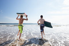 Teenagers surfing. In sea with surf boards royalty free stock images