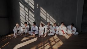 Teenagers at taekwondo school relax after an intense martial arts training. They chat sitting by the wall in white stock video footage
