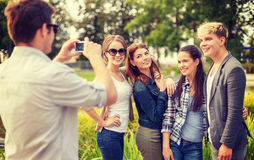 Teenagers taking photo with digital camera outside Royalty Free Stock Photography