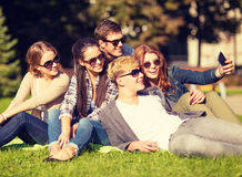 Teenagers taking photo outside with smartphone. Summer holidays and teenage concept - group of teenagers taking photo outside with smartphone Royalty Free Stock Photography