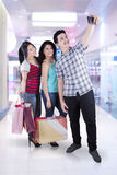 Teenagers taking pictures in the mall. Cheerful multiracial people with shopping bags taking pictures in the mall Stock Photo