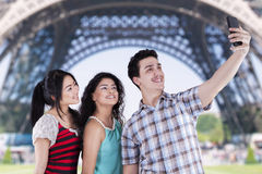 Teenagers taking self pictures in paris. Portrait of multiracial teenagers using smartphone to take self portrait near the Eiffel Tower Royalty Free Stock Image