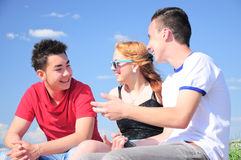 Teenagers talking outdoor. Threee interracial teenager friends, two boys and one girl,  talking and having fun outdoor, against blue summer sky Stock Images