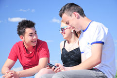Teenagers talking outdoor. Threee interracial teenager friends, two boys and one girl,  talking and having fun outdoor, against blue summer sky Stock Photos