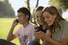 Teenagers talking on their cell phones. royalty free stock images