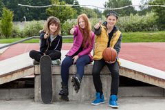 Teenagers thumbs up at skatepark Stock Images