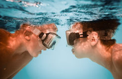 Teenagers under water. Two teenagers under water in masks Royalty Free Stock Photos