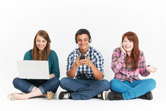 Teenagers Using Different Forms Of Digital Technology In Studio Stock Photo
