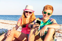 Teenagers are using smart phone and listening music. Technology and beach concept. Teenagers (boy and girl) using smart phone (mobile) and listening music with Stock Images