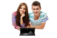 Teenagers using a tablet. Teenagers students friends sitting on floor using a tablet, isolated on white Stock Photos