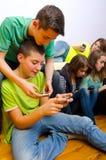 Teenagers using their mobile phones. Teenage friends playing with their mobile phones Royalty Free Stock Images