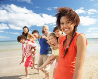 Teenagers walking on beach. Smiling at camera stock photo