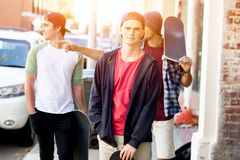 Teenagers walking down the street in summer day Royalty Free Stock Image