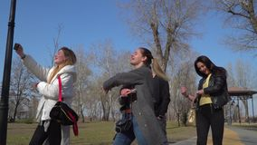 Teenagers walks in park and sings to the beat of music. Funny friends sings and dances at the street in park. Teenagers have fun together and moving to the beat stock footage