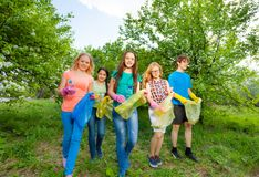 Teenagers wear gloves and carry garbage bag. S walking together in the forest royalty free stock photo