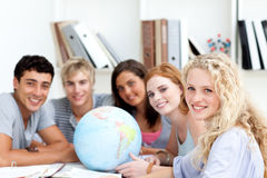 Teenagers working with a terrestrial globe. Smiling teenagers in a library working with a terrestrial globe and taking notes royalty free stock photo