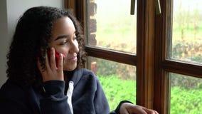 teenagersitting由窗口的愉快的微笑的美丽的混合的族种非裔美国人女孩谈话在她的流动手机 股票录像