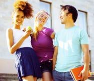 Teenages bonitos do grupo na construção da universidade com huggings dos livros Foto de Stock Royalty Free