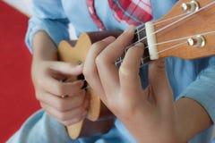 Teenages hand som spelar ukulelet Royaltyfri Foto