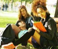 Teenages lindos del grupo en el edificio de la universidad con los huggings de los libros, naciones de la diversidad Fotos de archivo