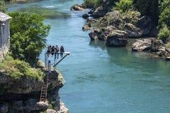 Teenages zit op een duik paltform over de rivier het letten op bestuurderssprong van Stari de Meeste brug stock afbeelding