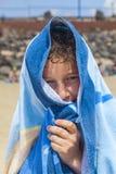 Teenboy con la toalla sobre su cabeza en la playa Fotografía de archivo libre de regalías