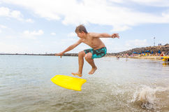 Teenboy enjoys surfing in the waves. Happy boy enjoys surfing in the waves at the beach stock images