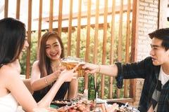 Teeneger asiatiska vänner som klirrar exponeringsglas, medan tycka om ett aftonmål i en restaurang arkivfoton