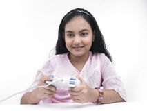 Teenger gamming. Asian teenage girl of indian origin playing with her play station Royalty Free Stock Photo