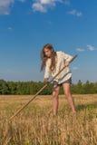 Teengirl con una guadaña en el campo del verano Imágenes de archivo libres de regalías