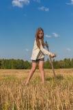 Teengirl con una guadaña en el campo del verano Foto de archivo