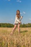 Teengirl con una guadaña en el campo del verano Imagenes de archivo
