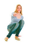Teengirl de sorriso que squatting e que aponta em você Foto de Stock Royalty Free