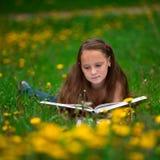 Teengirl läser en bok i ängen Fotografering för Bildbyråer