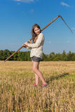 Teengirl with a scythe at summer field Royalty Free Stock Photo