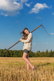 Teengirl with a scythe at summer field Royalty Free Stock Images