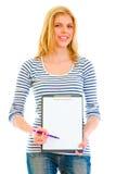 Teengirl sonriente con el sujetapapeles para firmar Imagen de archivo libre de regalías