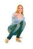 Teengirl sonriente que se pone en cuclillas y que señala en usted Foto de archivo libre de regalías