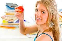 Teengirl sonriente que se sienta en el escritorio y sostener la manzana Fotografía de archivo