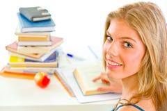 Teengirl sorridente che si siede alla tabella con i libri Fotografie Stock Libere da Diritti