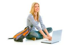 Teengirl sorridente che si siede sul pavimento e sul per mezzo del computer portatile Immagini Stock
